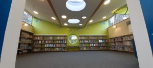 Inside the children's library at Honiton Library, redecorated in light green, high ceiling and circular windows