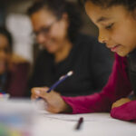 Mother and two daughters attending arts workshop, shown drawing and writing